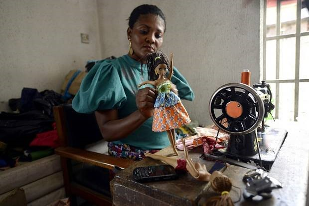 """A """"Queens of Africa"""" doll being dressed"""